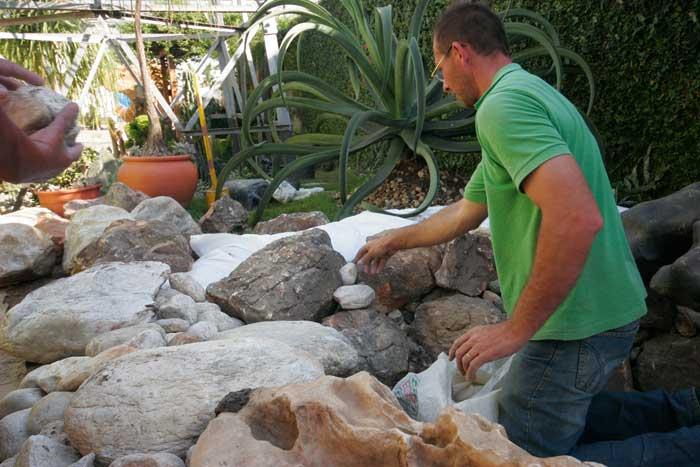 Seixos entre as pedras maiores no lago ornamental passo a passo