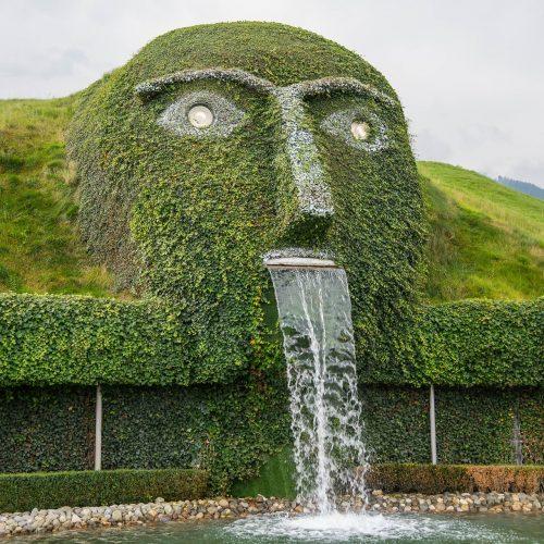 3. Cascata alta, do tipo lâmina d'água, surgindo de uma figura ou escultura.